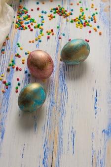 Концепция пасхи с пасхальными яйцами, конфетами, белой тканью на белой деревянной поверхности