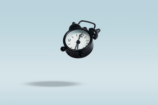 青色の背景に黒の目覚まし時計を飛んでいます。浮上。コンセプトタイム管理