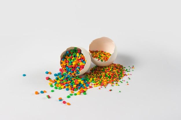 イースターのコンセプト。壊れた卵とイースターのカラフルな装飾は、白い表面のシェルから注ぎます。斜めに撮影