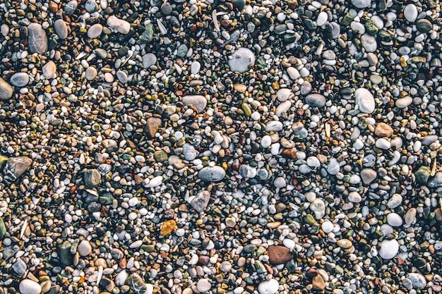 Пляж каменная галька. текстура мелких камней и песка. может использоваться в качестве текстуры фона