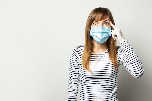 Молодая женщина в защитной медицинской маске и латексных перчатках держит палец у виска на светло-изолированной стене. жест думай, будь осторожен. карантин, средства правовой защиты, концепция коронавируса