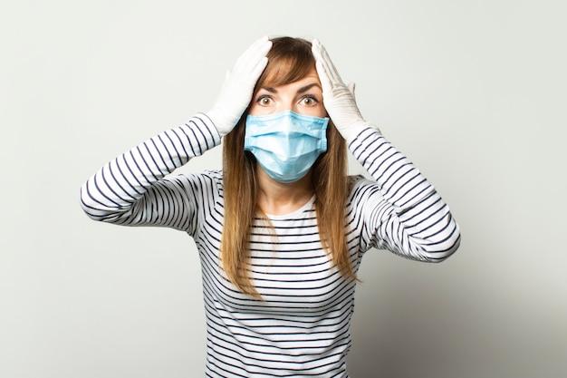 Молодая женщина в защитной медицинской маске и латексных перчатках держит голову в руках на свет изолированной стене. жест ужаса, будьте внимательны. карантин, средства правовой защиты, концепция коронавируса