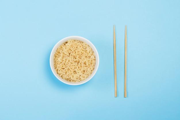 白い皿にアジアのインスタントラーメンと青い表面に中国の棒。コンビニ食品、ファーストフード、ジャンクフードの概念。フラット横たわっていた、トップビュー。