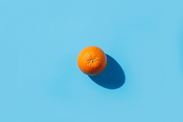 Один апельсин на синей поверхности. жесткий свет. концепция тропики, здоровое питание, завтрак, диета, отдых. плоская планировка, вид сверху.