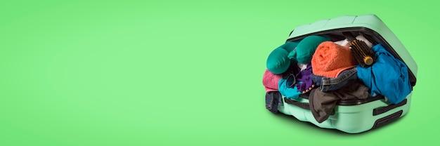 緑の背景にあふれている車輪が付いているプラスチックスーツケース。旅行の概念、休暇旅行、親戚への訪問。バナー