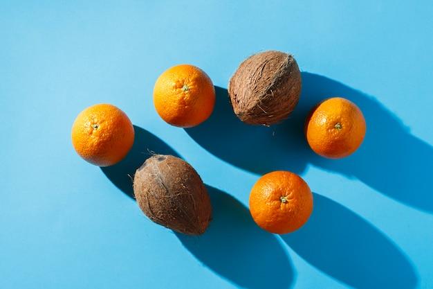 Апельсины и кокосы на синей поверхности. жесткий свет. концепция тропики, здоровое питание, завтрак, диета, отдых. плоская планировка, вид сверху.