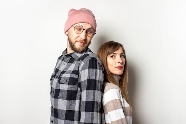 帽子のひげと格子縞のシャツの若い男とセーターの女の子は、孤立した明るい背景に背中合わせに立っています。男性は女性を見ます。