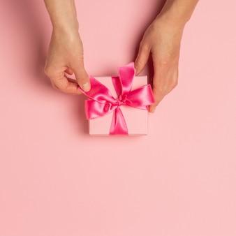 女性の手はピンク色の表面につかまって、贈り物を受け取ります。バレンタイン・デー