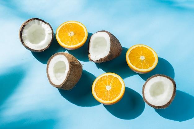 影付きの自然光の下で青い表面にオレンジとココナッツ。ハードライト。ダイエット、健康的な食事、熱帯の休暇、休暇、旅行の概念。