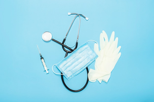 医療聴診器、ラテックス手袋、注射器、青色の背景に防護マスク。コンセプト医学、看護師、病院、安全性、流行。バナー。フラット横たわっていた、トップビュー