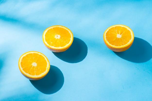 Апельсины на синей поверхности при естественном освещении с тенями. жесткий свет. концепция диеты, здорового питания, отдыха в тропиках, отдыха и путешествий, витамины.