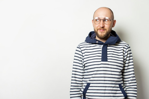 Лысый молодой человек с бородой в очках жакет с капюшоном смотрит в сторону на изолированных белый.