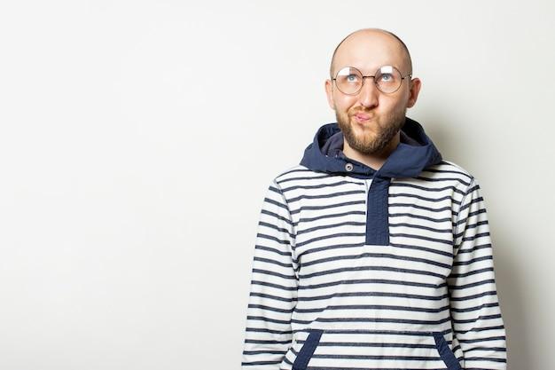 Лысый молодой человек с бородой в очках пиджака с капюшоном смотрит на изолированных белый. жест думать, планировать, мечтать