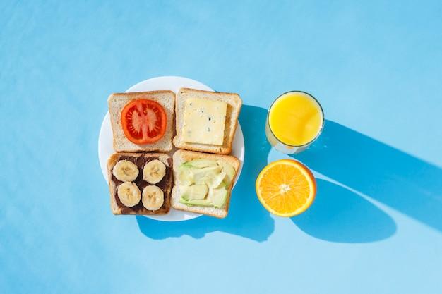 白い皿にサンドイッチ、オレンジジュースとガラス、青い表面。フラット横たわっていた、トップビュー。