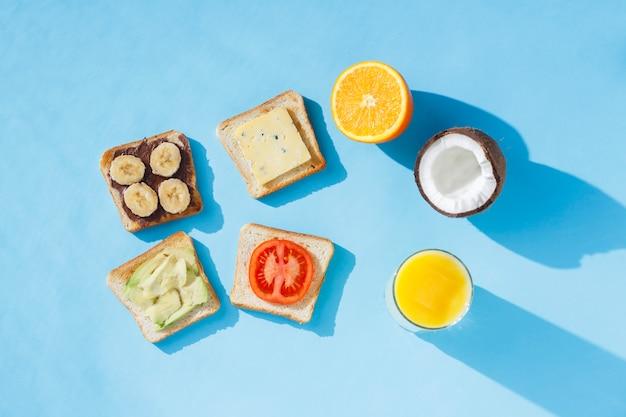 サンドイッチ、オレンジジュース、ココナッツ、オレンジ、青い表面のガラス。フラット横たわっていた、トップビュー。