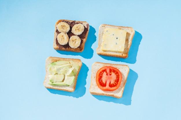 Бутерброды с сыром, помидорами, бананом и авокадо на синей поверхности. плоская планировка, вид сверху.