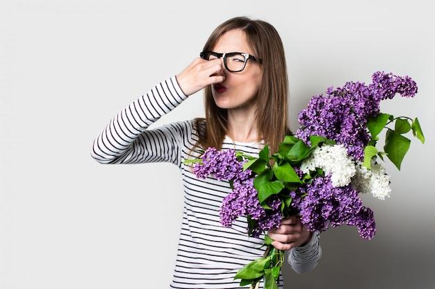 Молодая женщина держит сирень ущипнула нос пальцами, аллергия на цветы, на светлом фоне.
