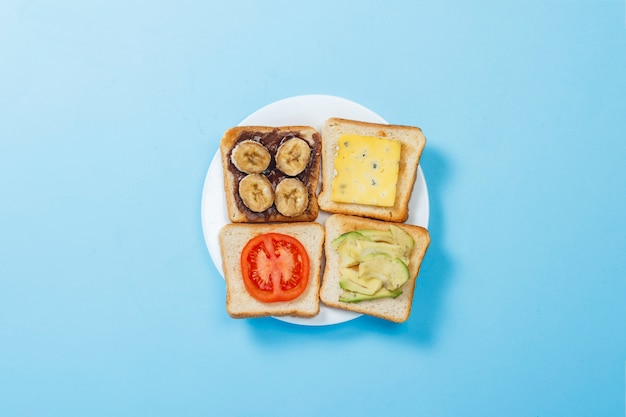 Бутерброды с сыром, помидорами, бананом и авокадо на белой тарелке, синей поверхности. плоская планировка, вид сверху.