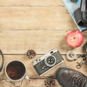 Обувь, фотоаппарат, кружка с горячим чаем, рюкзак, карта и компас на деревянной поверхности. концепция походов в горы или лес, туризм, палаточный отдых. плоская планировка, вид сверху.