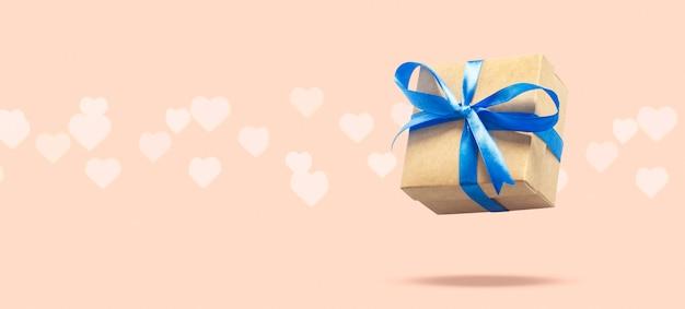 Подарочная коробка летая на светло-розовой поверхности с боке в форме сердца. концепция праздника, подарок, продажа, свадьба и день рождения.