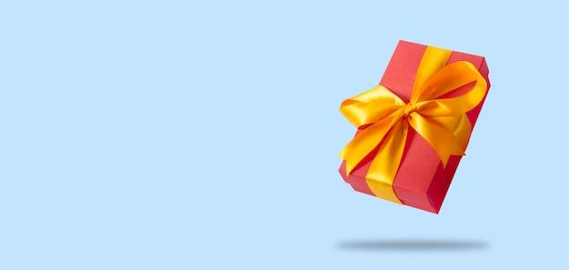 Летающая подарочная коробка на светло-голубой поверхности. концепция праздника, подарок, продажа, свадьба и день рождения.