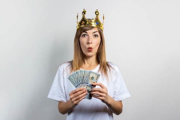 Молодая женщина с короной на голове и удивленным лицом держит стопку денег на светлом фоне