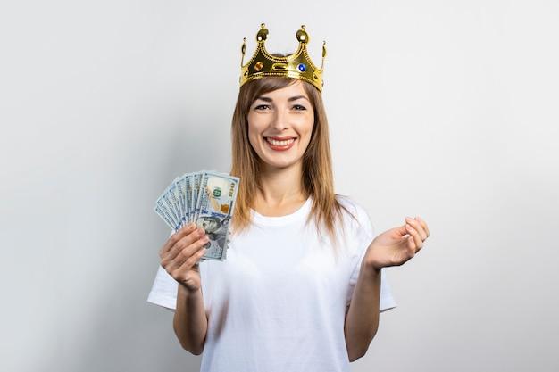 Молодая женщина с короной на голове держит пачку денег и очень радостно празднует на светлом фоне