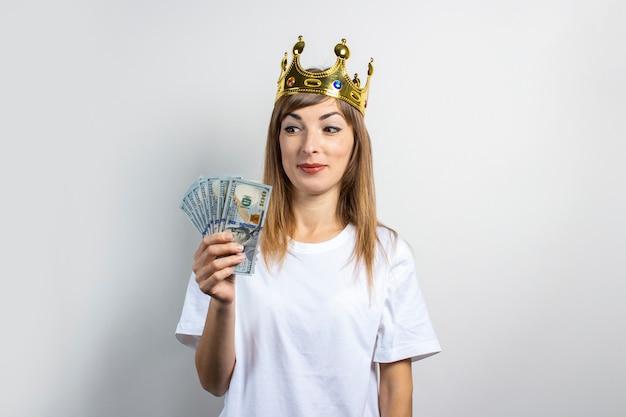 Молодая женщина с короной на голове держит пачку денег и на светлом фоне