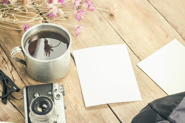 Полевые цветы, металлическая чашка чая, компас и другие атрибуты для похода по деревянной поверхности. концепция походов в горы или лес, туризм, палаточный отдых, лагерь. плоская планировка, вид сверху.