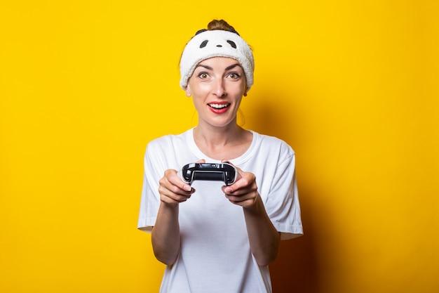 Молодая женщина играет в виртуальную игру с джойстиком в руках.