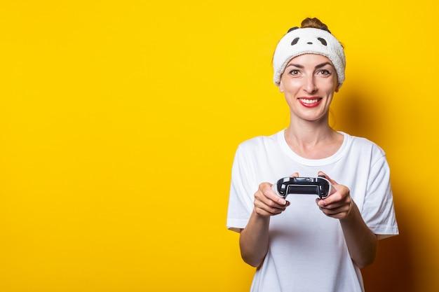 Молодая усмехаясь женщина играя виртуальную игру с джойстиком в их руках.