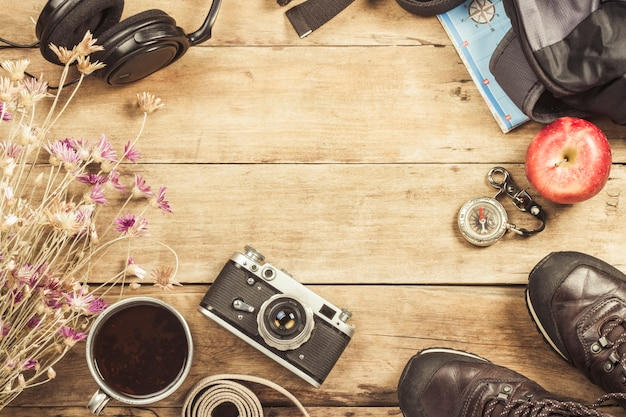 Ботинки, рюкзак, компас и другое туристическое снаряжение на деревянной поверхности. концепция походов в горы или лес, туризм, палаточный отдых, лагерь. плоская планировка, вид сверху.