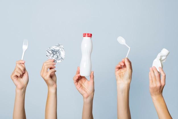 手は明るい空間にゴミを保持します。ゴミを分別する、プラスチックをやめる、リサイクルのコンセプト。