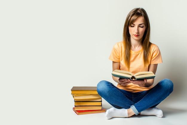 若い女性は、明るい空間の床に座って本を読んでいます。教育コンセプト、試験準備。バナー。