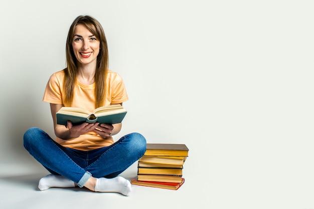 若い女性は、明るい空間の床に座って本を持っています。教育コンセプト、試験準備。バナー。