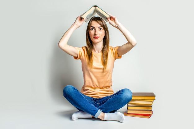 明るい空間の床に座っている間、女性は本を持っています。教育コンセプト、試験準備。バナー。