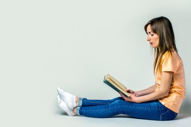 若い女性は床に座って、明るい空間で本を読みます。バナー