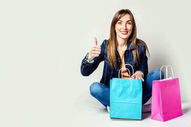 デニムジャケットを着た笑顔の女性が、明るい空間の床に座って買い物袋を持ってジェスチャーをします。すべてがスーパーです。バナー。コンセプトショッピング、販売。