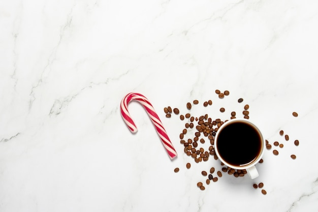 コーヒーのカップと大理石のテーブルにハート型のキャラメル杖。コンセプトディナー、バレンタインの日、日付、会議、コーヒーの愛、休日、クリスマスイブ
