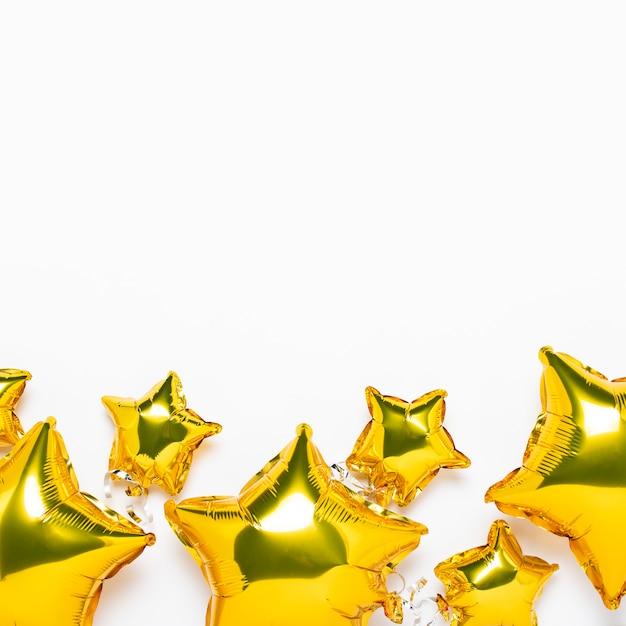 空気黄金の風船星の形と白いスペースのお菓子。休日、パーティー、写真ゾーン、装飾のコンセプトです。バナー。フラット横たわっていた、トップビュー