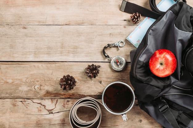 Походный рюкзак, компас, ремень и другое туристическое снаряжение на деревянной поверхности. концепция походов в горы или лес, туризм, палаточный отдых, лагерь. плоская планировка, вид сверху.