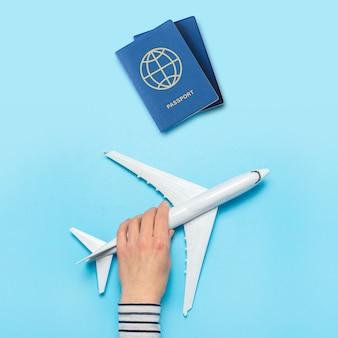 女性の手は青い空間に飛行機とパスポートを保持しています。コンセプトフライト、チケット、予約、フライト検索、旅行