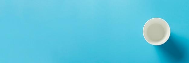 青い空間で飲み物のための空の紙コップ。バナー。フラット横たわっていた、トップビュー
