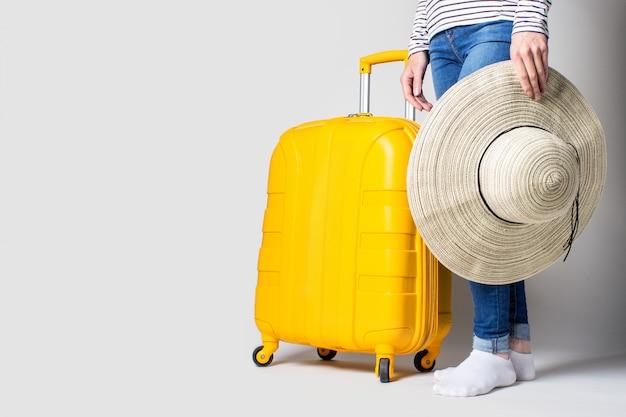女性は明るい空間で黄色のプラスチック製のスーツケースと太陽からの帽子を持っています。旅行の概念、フライトの期待、休暇。脚だけが見える