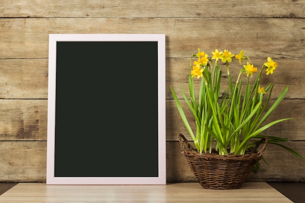 木製の表面に透明な板と春の花の入った花瓶。春、休日の始まりの概念。コピースペース。