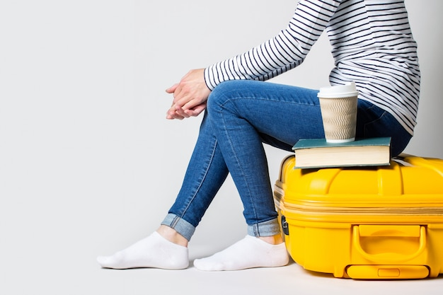 女性は、コーヒーと明るい空間の本とガラスの近くの黄色のプラスチックスーツケースに座っています。フライト、休暇、空港を待っている旅行の概念