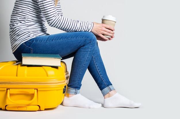 女性は一杯のコーヒーを保持し、明るい空間で黄色のプラスチックスーツケースに座っています。旅行の概念。