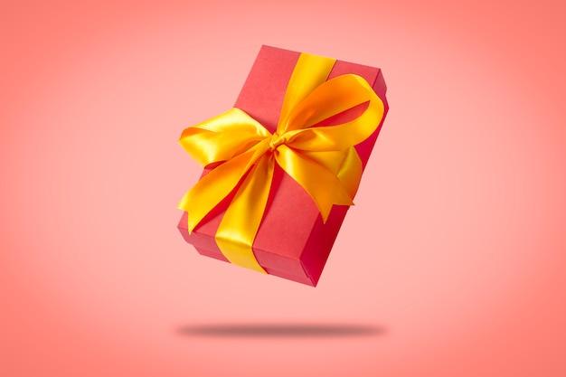 明るいピンクの表面に飛んでいるギフトボックス。休日の概念、ギフト、販売、結婚式、誕生日。