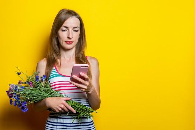 美しい少女は携帯電話を見て、野生の花の花束を保持しています。