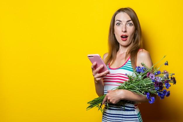 電話と花の花束を持つ驚いた少女